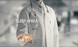 "A medical professional holding out his hand with a digital image appearing of the words ""Sleep Apnea"""