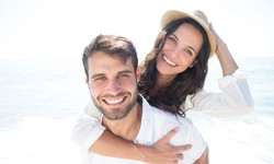 couple smiling on beach after dental bonding in Tulsa