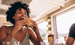 Woman smiling while eating burger at restaurant