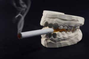 teeth mold holding a cigarette