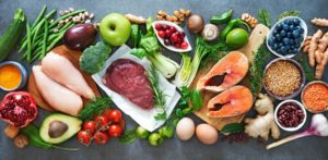 a spread of healthy foods including fish, lean meats, fruits, and vegetables