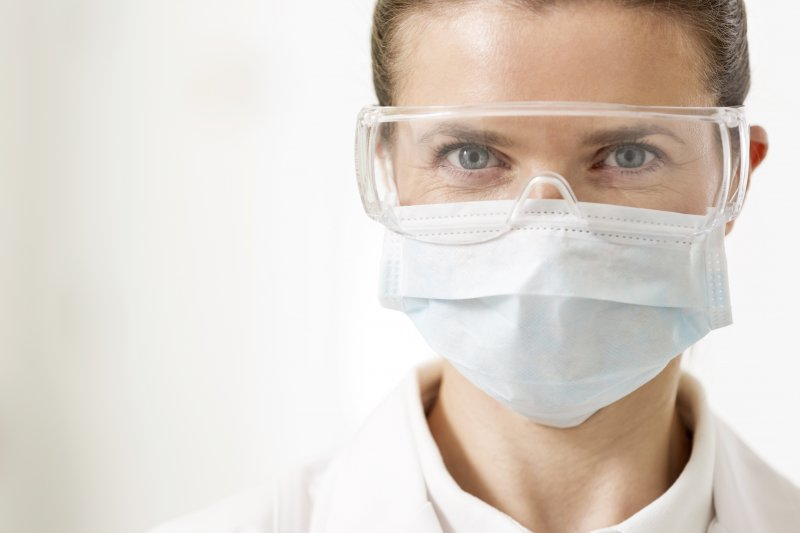 a dentist wearing protective eyewear, lab coat, and a face mask