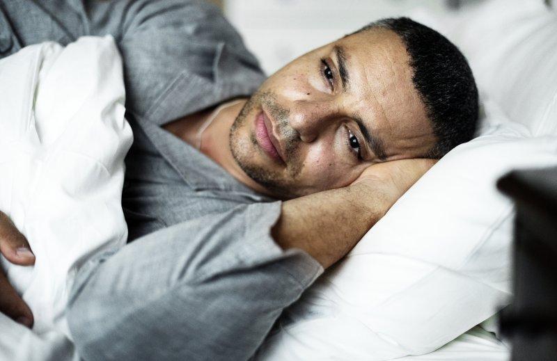 Anxious man with sleep apnea lying awake in bed